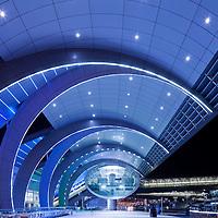 United Arab Emirates, Dubai, Glowing lights outside modern architectural exterior of Dubai International Airport Terminal 3