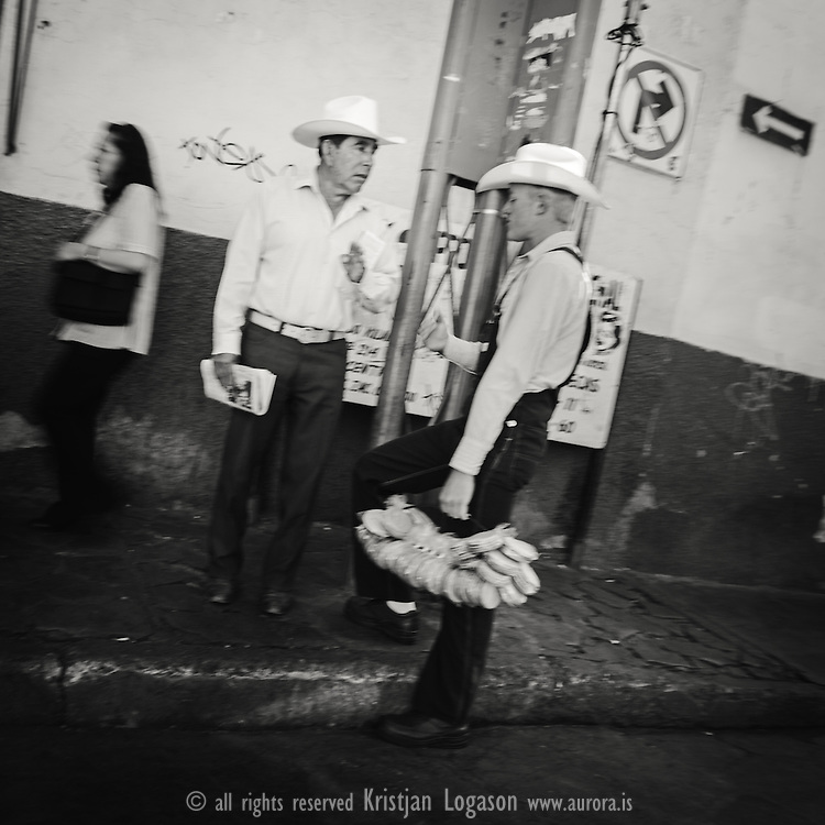 Two men with hats one with bunch of bread in his hand standing in the street talking