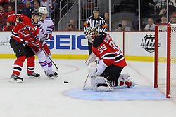 Sep 16, 2013; Newark, NJ, USA; New Jersey Devils goalie Cory Schneider (35) makes a save while New York Rangers right wing Arron Asham (45) looks for the rebound during the first period at Prudential Center.