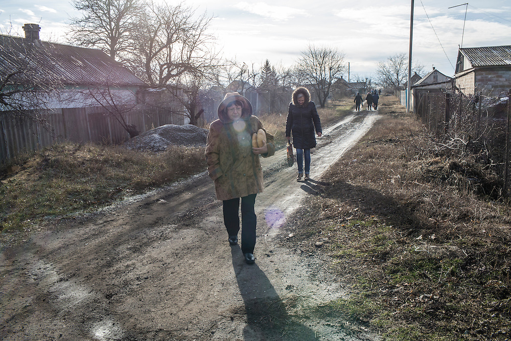Local residents receive free bread delivered by the Good Word Protestant Church in need on Thursday, December 10, 2015 in Mariinka, Ukraine.