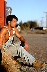 hunk without a shirt wearing overalls sitting outdoors in the afternoon sun in rural America