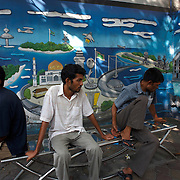 In the shade of mid-day heat near a mural, Maldivian youths sit about on a park bench in the Maldives capital Male.