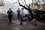 A neighbor stands while Civil Guard officers work on a forest fire that reached a house in San Agustin de Guadalix on August 11, 2012, near Madrid, Spain. During a heat wave dozens of forest fires have appeared in Spain, three of them at National Parks, like Teide, Doñana or Cabañeros, and also thousands of people had to be evacuated at La Gomera and Tenerife, in the Canary Islands.