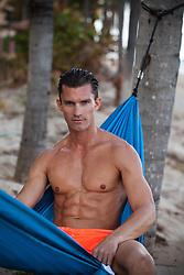 good looking man at the beach in a hammock