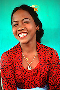 INDONESIA, BALI, CEREMONIES portrait of a young Balinese woman showing her smile after a tooth filing ceremony