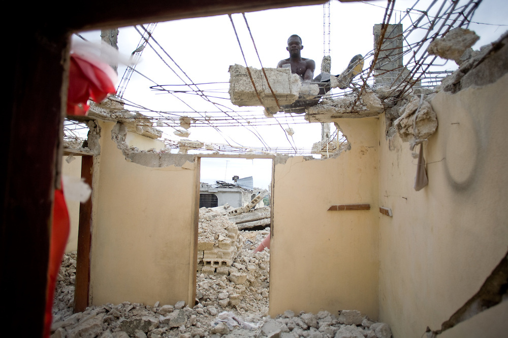 A man breaks apart a building destroyed in the earthquake with a hammer. This man is working by the day earning 5oo Gourdes a day approximately $12.50 USD.