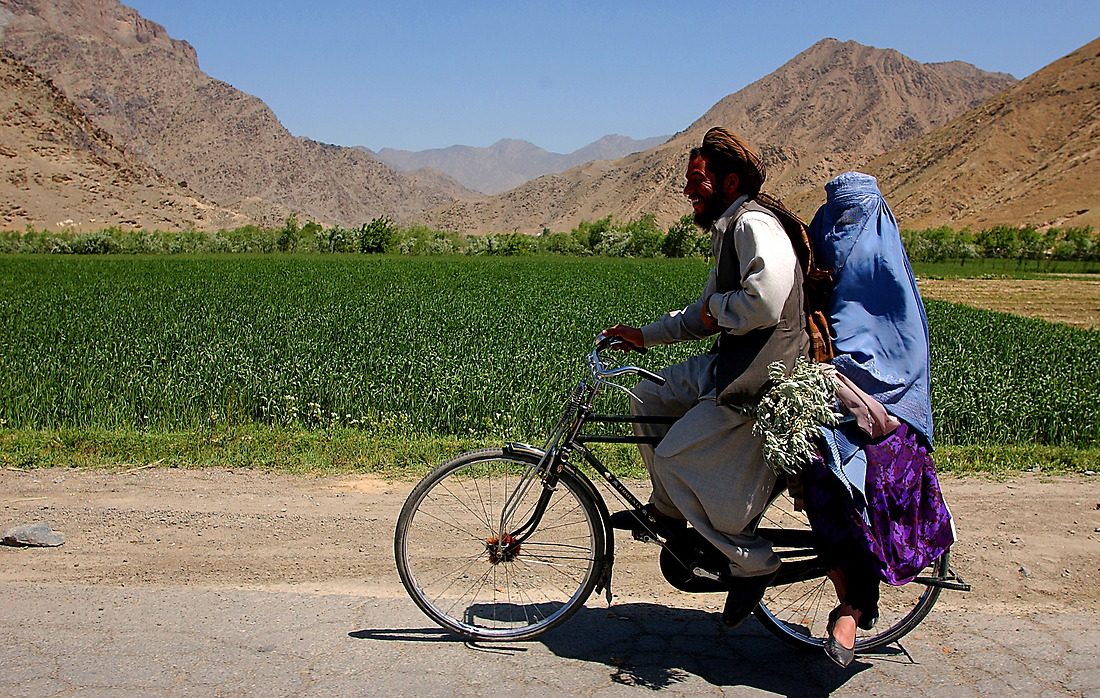 An Afghani couple rides through the streets of Kabul as a U.S. convoy passes them on their way to Gardez on May 10, 2002 in support of Operation Enduing Freedom. — © /