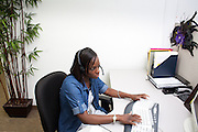 Adrienne Martin, a customer service agent, advises a student of their financial aid status for Troy University from the Greenwood Hall call center in Bryan, Texas. <br />