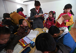 A volunteer teacher helps migrant children with their homework at a newly opened community centre built out of shipping containers by non-profit organisation Compassion for Migrant Children (CMC) in a migrant community in Beijing, China on 24 March 2011. CMC started the mobile community centre for migrant children and their families from containers custom made to fit as classrooms, computer labs, and offices. This is the first time the non-profit organisation sets up a new container community centre to cater to the growing needs of migrant workers in the city who are often forced to move when the area they live in are redeveloped or demolished. The community centre offers vocational training for youths, extracurricular activities for children, training for new mothers and family health.