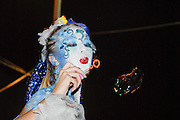 young female model with make up mask blows bubbles.