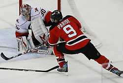 Apr 15, 2009; Newark, NJ, USA; Carolina Hurricanes goalie Cam Ward (30) makes a save on New Jersey Devils left wing Zach Parise (9) during the second period of game one of the eastern conference quarterfinals of the 2009 Stanley Cup playoffs at the Prudential Center.