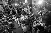 Singing hymns with a crowd outside the church, Carolyn Richardson, center, raises her hand in reverence to Jesus on June 19, 2015.