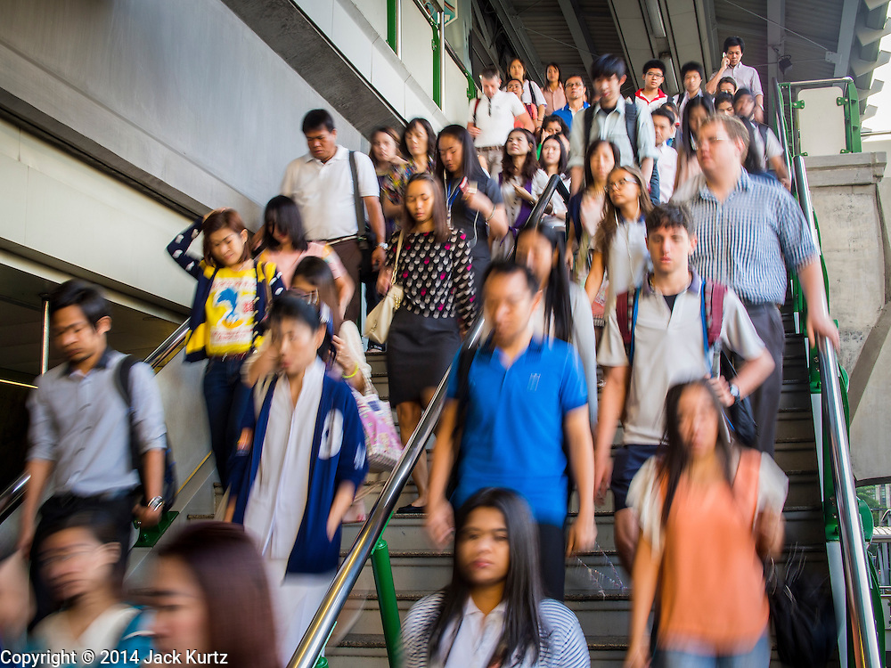 19 NOVEMBER 2014 - BANGKOK, THAILAND: Commuters leave the Asoke BTS Skytrain station in Bangkok. Between July and September the economy expanded 0.6 percent compared to the previous year, the National Economic and Social Development Board (NESDB) reported. Thailand's economy achieved a weak 0.2 per cent growth across the first nine months of the year. The NESDB said the Thai economy is expected to grow by 1 percent in 2014. Authorities say the sluggish growth is because tourists have not returned to Thailand in the wake of the coup in May, 2014, and that reduced demand for computer components, specifically hard drives, was also hurting the economy. Thailand is the leading manufacturer of computer hard drives in the world. The Thai government has announced a stimulus package worth $11 billion (US) to provide cash handouts to farmers and promised to speed up budget spending to boost consumption.   PHOTO BY JACK KURTZ