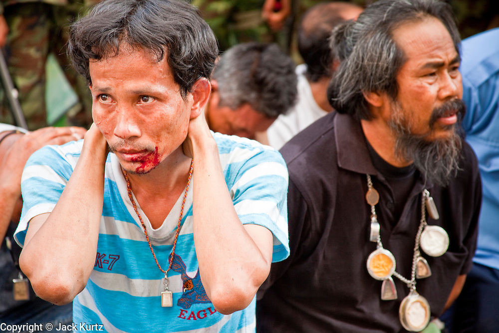 14 MAY 2010 - BANGKOK, THAILAND: A man with a split lip and bloodied face sits in the custody of Thai troops Friday afternoon on Rama IV Road. Thai troops and anti government protesters clashed on Rama IV Road Friday afternoon in a series of running battles. Troops fired into the air and at protesters after protesters attacked the troops with rocket and small homemade explosives. Unlike similar confrontations in Bangkok, these protesters were not Red Shirts. Most of the protesters were residents of nearby Khlong Toei slum area, Bangkok's largest slum area. The running battle went on for at least two hours.   PHOTO BY JACK KURTZ
