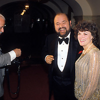 Comedia Dom Deluise with wife Carol Arthur wait while photographer Harry Naltchayan loads film into his camera at the White House on February 28, 1984.