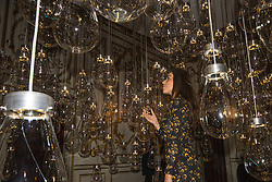 London, September 18th 2015. A woman interacts with Curiosity Cloud by mischer&rsquo;traxler for Perrier-Jouet. The installation comprises 250 mouth-blown glass globes hang from the ceiling. Each bulb contains a single, hand-made insect. <br /> From a distance the insects are calm but as visitors approach, they come to life, fluttering and trilling as they batter the glass that contains them. The Victoria and Albert museum celebrates the London Design Festival which runs from 19 &ndash; 27 September, with a collection of conceptual installation artworks.
