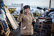"Pensioner Hanna posing in front of the barricades blocking a building supplies store named ""Epicenter"" in the city of Lviv, Ukraine."