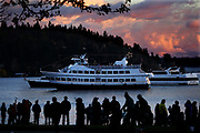 """At sunset, a crowd along the shore at Seward Park watches the """"Spirit of Seattle,"""" equipped with its own tree for the Argosy Cruises Christmas Ship Festival in Seattle. (Ken Lambert / The Seattle Times)"""