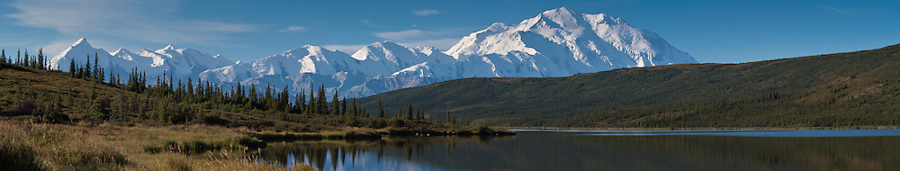 Sun rises on Mount McKinley and the Alaska Range as seen from Wonder Lake in Denali National Park and Preserve in Alaska. Mount McKinley also known as Denali is North America's tallest peak at 20,310 feet and towers over 18,000 feet above the surrounding lowlands. Other mountain peaks pictured include: Mount Brooks, Mount Silverthrone, Mount Tatum, and Mount Carpe. SPECIAL NOTE: This image is a panorama composite consisting of multiple overlapping images stitched together.