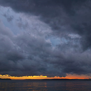 A dark storm cloud stretches over Puget Sound at sunset in this view from Alki Beach, Seattle, Washington.