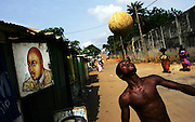 An Ivorian teen heads a ball to pass the time in the Adjame neighborhood of Abidjan, Ivory Coast February 17,2006. Football is an integral part of the social fabric that makes up Ivorian society.