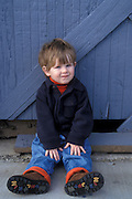 2 year old boy sitting in front of wood wall; Oakland, Oregon.