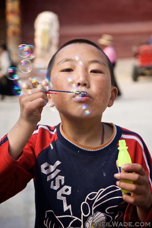 A Tibetan boy blows bubbles in Dege, Tibet.