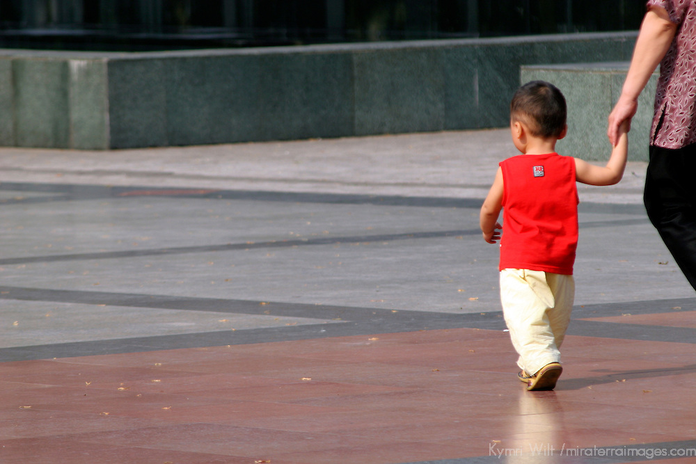 Asia, China, Chongqing. A young toddler walking with parent's hand.