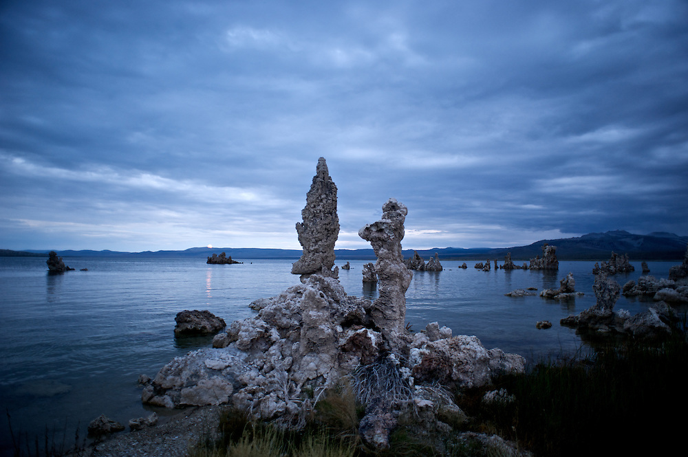 Tufa is a type of limestone that is formed when calcium-rich spring water mixes with the carbonate-rich Mono Lake water and precipitates around the spring. The towers grow underneath the waters surface. These towers were exposed when the city of Los Angeles diverted four of the five streams flowing into Mono Lake.  Deprived of its freshwater sources, the lake volume dropped by half, exposing nesting colonies of gulls to predation and again doubling the lakes salinity. The entire eco-system began to collapse. In response David Gaines formed the Mono Lake Committee, a citizens group that was formed to reverse this trend and save the lake. In 1994 the California Supreme Court mandated that the lake should rise to a level of 6,392 feet, which will partially restore the ecosystem and migratory bird habitat.<br /> <br /> In this photo, tufa towers stand beneath a cloudy sky as the full moon rises in the distance.