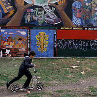 A boy rides his scooter past a colorful mural in Manhattan's Lower East Side in the 1980s.