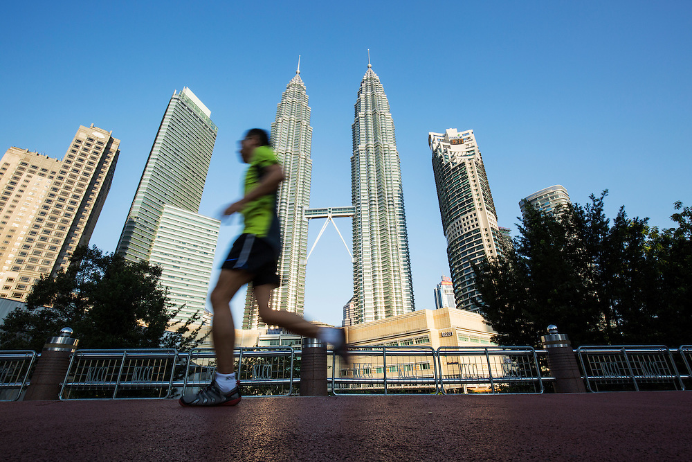 Malaysia, Kuala Lumpur, Low angle view of jogger running on trail in public park beneath 88 story tall Petronas Towers skyscrapers
