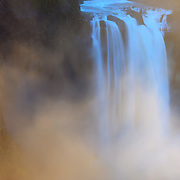 The late afternoon sun lights up the mist resulting from the force of Snoqualmie Falls, a 268-foot waterfall located near Snoqualmie, Washington. Snoqualmie Falls is one of the most popular tourist destinations in Washington state.
