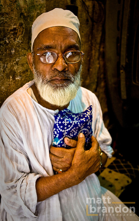A Muslim men holds his Quran to his chest in deep thought.