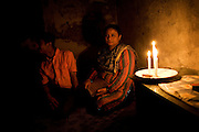 Amna Butt and her son Abdul sit in the lounge of their home in the 'Old City' district of Lahore. ..'Load-shedding' or power outages have resulted in families resorting to small, gas powered lamps or candles for those unable to afford gas lamps...The price of candles has doubled in recent days (10Rps per candle) as demand in lieu of load shedding increases..