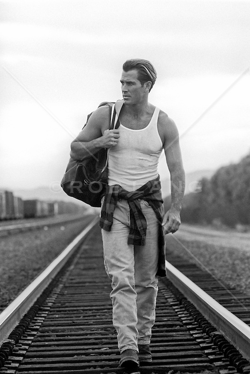 handsome rugged man walking a railroad track in New Mexico