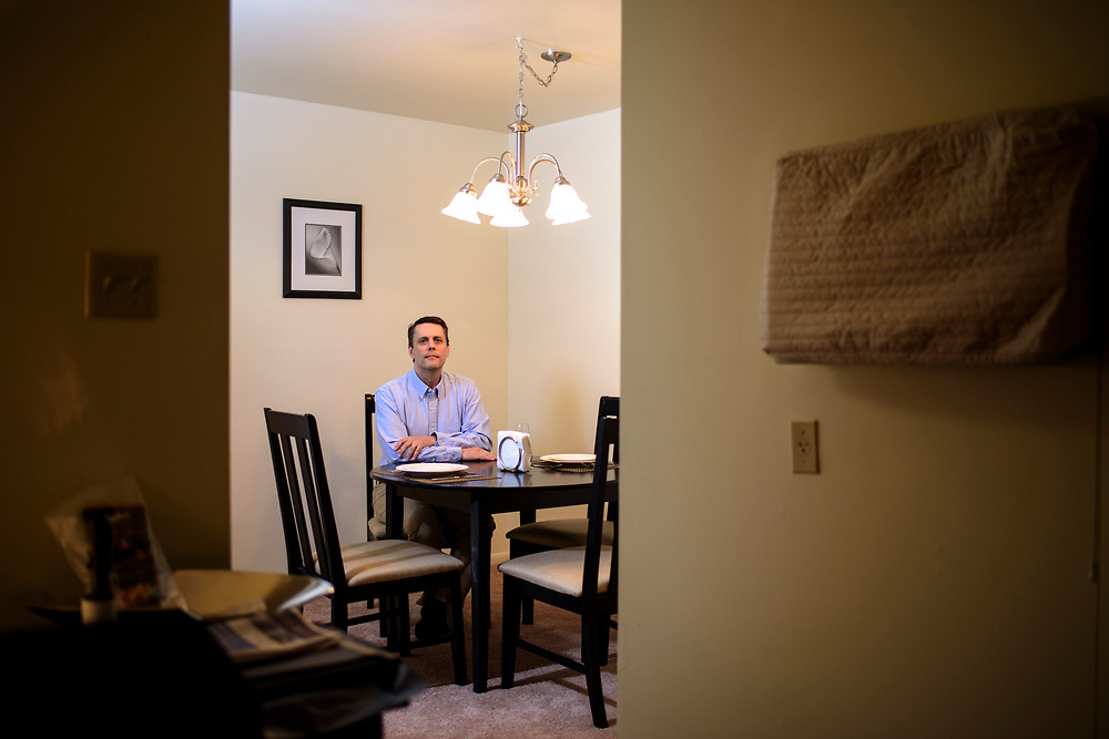 Lancaster, Pennsylvania - April 06, 2017: Russell Abney, is photographed in his temporary corporate apartment in Lancaster, Pa., Thursday April 6, 2017. In November 2016, he was laid off from his job in Toledo, Ohio, as a manufacturing engineer for First Solar, a U.S. based manufacturer of Solar Panels. Chinese manufactured solar panels undercut American made panels. As a result of profit loss, First Solar laid off 450 workers, Abney being one of them. He found a job in Lancaster as a manufacturing engineer for a ceiling panel company. <br /> <br /> <br /> CREDIT: Matt Roth for The New York Times<br /> Assignment ID: 30204974A