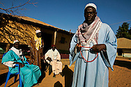 """Men chat and wait around the house of the holy man in Bafata-Oio village, Aladji Fode Mai Toure, expecting his blessing and listening to his advice. Locally known as """"Homem Grande"""", meaning 'great man', serving as a community and local leader. Half of the population are considered to be muslim."""