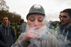 Hyde Park, London, April 19th 2015. Hundreds of cannabis users and their supporters gather at Speaker's Corner in Hyde Park for the annual London 420 pro-cannabis rally, under the watcful eye of Metropolitan Police officers, who kept a reasonably low profile, allowing the rally to continue without any serious incidents. PICTURED: A young woman in a polceman's helmet enjoys a smoke.