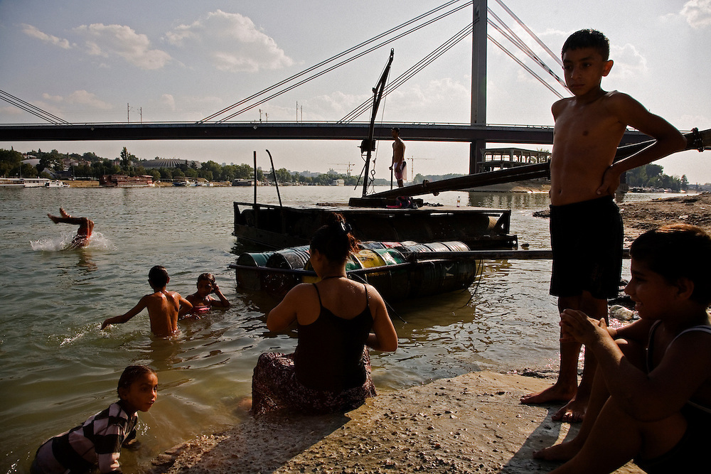 Families swim in the polluted Sava river to get away from the Belgrade summer heat and to bathe. Near the Nova Gazela settlement.