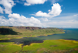 The shores of Lake Argyle are lined with lush grass in the Kimberley wet season.