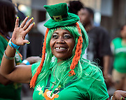 Dressed as a leprechaun Jackie Robinson of Atlanta waves to friends as she walking along River Street during the start of a four-day St. Patrick's Day celebration Saturday, March 14, 2015, on River Street in Savannah, Ga. Thousands of visitors are in Savannah this weekend to kick off a celebration that peaks Tuesday with the St. Patrick's Day parade. (AP Photo/Stephen B. Morton)
