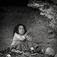 Young tarahumara girl seeking shelter from the sun in a cave while resting from helping here mother selling souvenirs