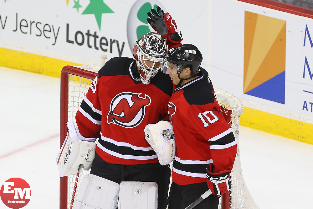 Mar 31, 2014; Newark, NJ, USA; New Jersey Devils defenseman Peter Harrold (10) congratulates New Jersey Devils goalie Cory Schneider (35) after the Devils 6-3 win over the Florida Panthers at Prudential Center.