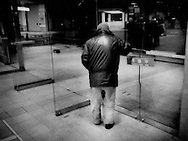 An elderly homeless man looks out into the night from a heated entrance to Shinjuku Station,  Tokyo, Japan.  He will have to spend the night out there after the last train departs and the station closes its doors.  Tokyo train stations and parks have become de facto dumping grounds for untold numbers of unwanted old men.