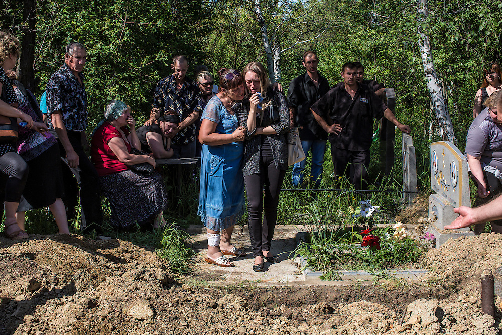 HORLIVKA, UKRAINE - MAY 24: Relatives grieve at the graveside during the funeral of Aleksandr Politov, a pro-Russia militia fighter who was killed when his group attacked a Ukrainian military checkpoint two days earlier in the village of Blahodatne, on May 24, 2014 in Horlivka, Ukraine. Presidential elections are scheduled for tomorrow, but pro-Russia militias have been seeking to prevent them from being administered throughout the eastern part of the country. (Photo by Brendan Hoffman/Getty Images) *** Local Caption ***