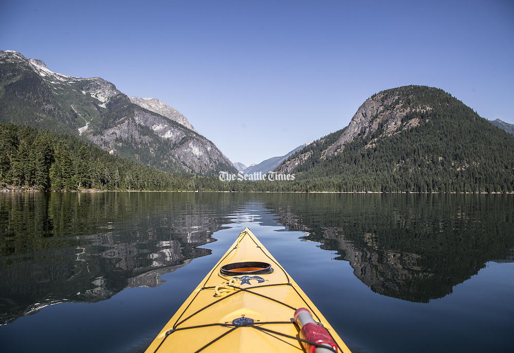 Kayaking on Ross Lake between the shadows of an unidentified peak at left and Pumpkin Mountain at right. In the saddle between is the Big Beaver Creek trail in the North Cascades National Park.<br />