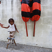 "Trinidad and Tobago ""MOKO JUMBIES: The Dancing Spirits of Trinidad"".(Dragon Glen De Souza's  two year old son Mutawakkil is the youngest MokoJumbie in the yard. He loves to be on stilts as he watches the older students, who in turn teach and protect him. His mother Luanna Williams, left, herself an experienced Moko Jumbie, always stays close.).A photo essay about a stilt walking school in Cocorite, Trinidad..Dragon Glen de Souza founded the Keylemanjahro School of Art & Culture in 1986. The main purpose of the school is to keep children off the streets and away from drugs..He first taught dances like the Calypso, African dance and the jig with his former partner Cathy Ann Samuel.  Searching for other activities to engage the children in, he rediscovered the art of stilt-walking, a tradition known in West Africa as the Moko Jumbies , protectors of the villages and participants in religious ceremonies. The art was brought to Trinidad by the slave trade and soon forgotten..Today Dragon's school has over 100 members from age 4 and up..His 2 year old son Mutawakkil is probably the youngest Moko Jumbie ever. The stilts are made by Dragon and his students and can be as high as 12-15 feet. The children show their artistic talents mostly at the annual Carnival, which today is unthinkable without the presence of the Moko Jumbies. A band can have up to 80 children on stilts and they have won many of the prestigious prizes and trophies that are awarded by the National Carnival Commission. Designers like  Peter Minshall , Brian Mac Farlane and Laura Anderson Barbata create dazzling costumes for the school which are admired by thousands of  spectators. Besides stilt-walking the children learn the limbo dance, drumming, fire blowing and how to ride  unicycles..The school is situated in Cocorite, a suburb of Port of Spain, the capital of Trinidad and Tobago..all images © Stefan Falke"