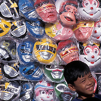 Philippines, Panay Island, Boy stands in front of stand selling masks at Ati-Atihan Festival in downtown Kalibo.