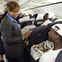 Oregon Ducks football team prepares for trip and travels to Oklahoma for game against against the Sooners. Flight attendant gives five to player..Photos © Todd Bigelow/Aurora