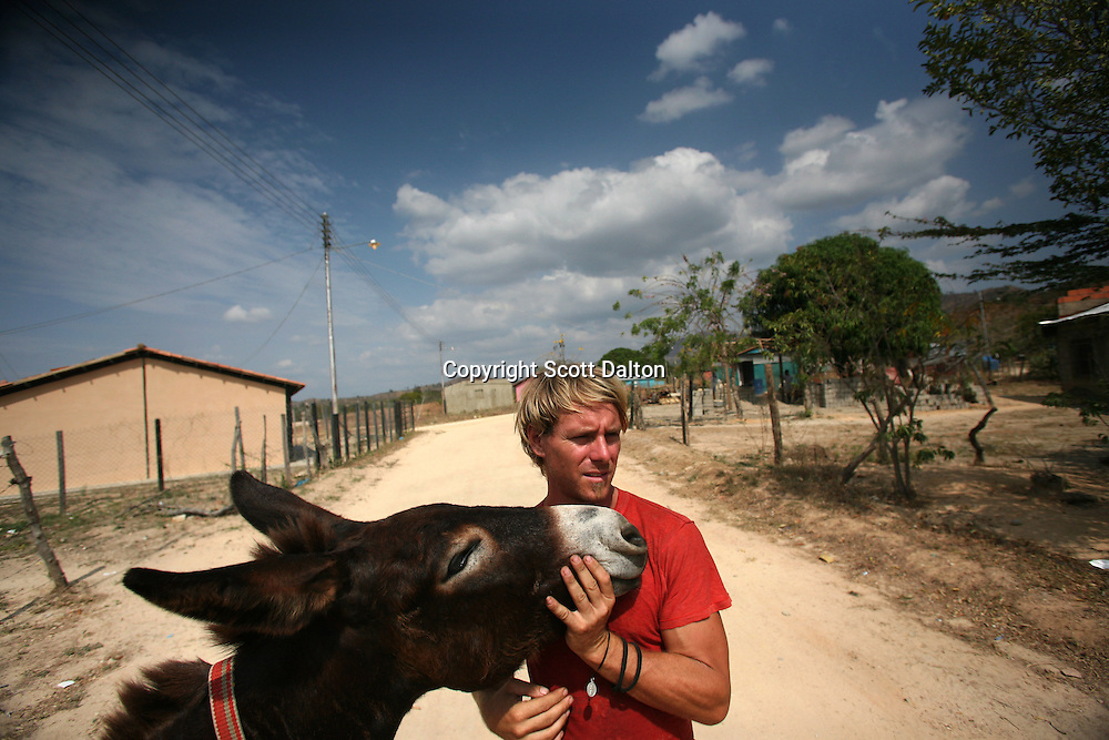 Jonathan Dunham, 33, of Laramie, Wyoming holds his donkey that he calls Whothey in English but Judas in Spanish, in a poor barrio in Tinaco, Venezuela on Sunday, February 10, 2008. Durham has been walking for the past two years, starting in Oregon. In Mexico he was given the donkey with which he has made the rest of the trek. He plans to continue walking to the tip of Argentina. (Photo/Scott Dalton).